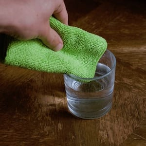 Microfiber cloth being dipped in water to clean an iPad screen.