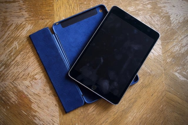 iPad with a dirty screen rested on top of an iPad case.
