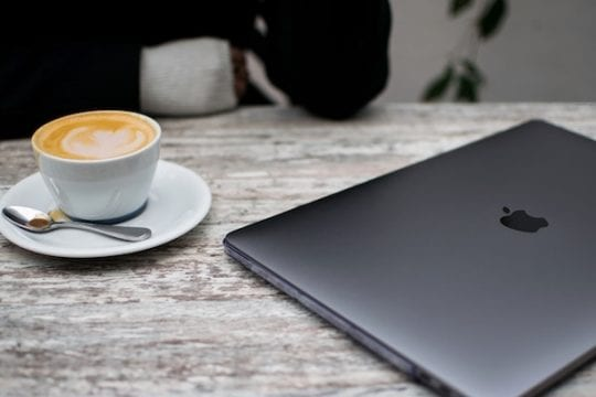 A closed MacBook next to a cup of coffee