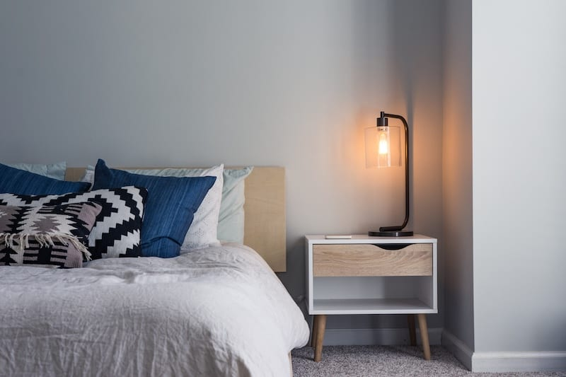 Photo of a minimalist bedroom showing a neat bed and a softly glowing bedside lamp