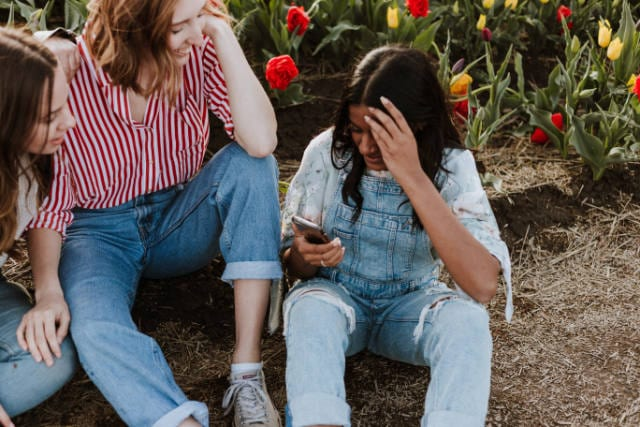 Three girls talking about an iPhone