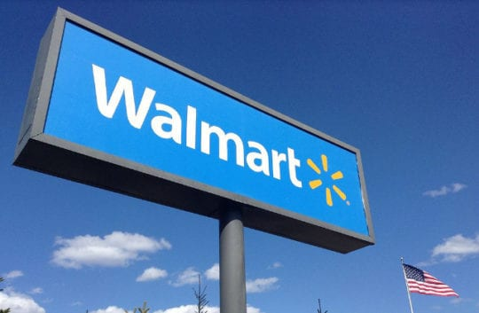 Walmart sign next to an American flag in front of a blue sky