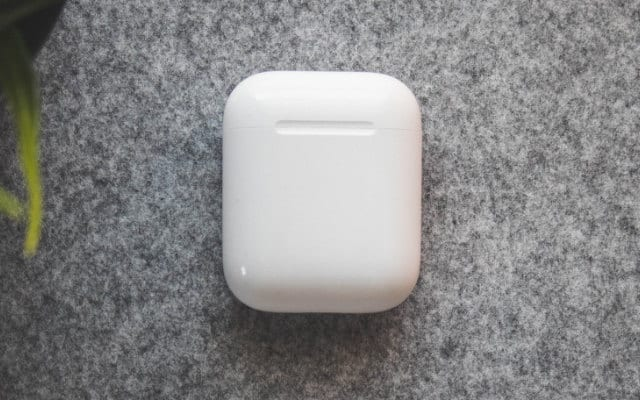 AirPods charging case closed on grey surface