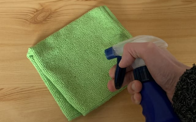 Spraying water onto a microfiber cloth