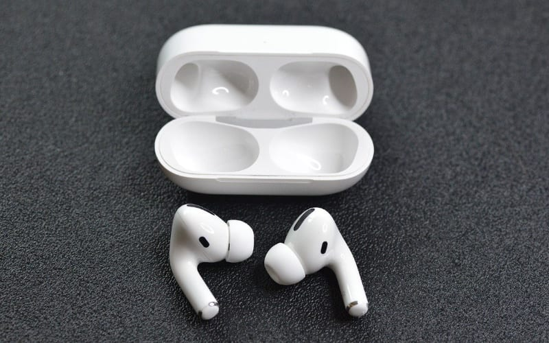 AirPods Pro on gray background next to charging case