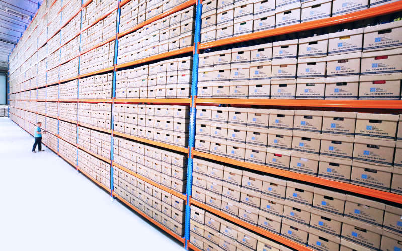 Rows of shelves of archive boxes in a warehouse